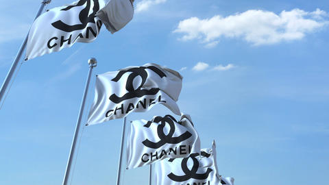 Waving flags with Chanel logo against sky, seamless loop. 4K editorial animation Image