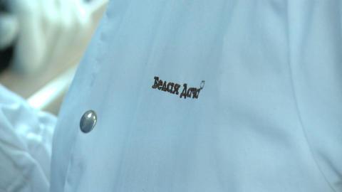 Closeup Belaya Dacha Logo on Trainer White Sterile Coat Live Action