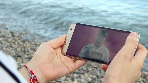 Girl Watching YouTube on Her Smartphone on the Beach Image