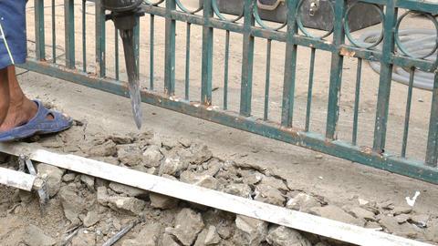 Worker breaking cement floor by using demolition hammer Footage
