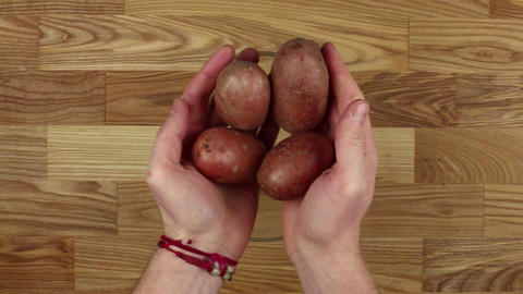 Man holding potatoes in his hands ビデオ