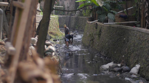 Local community collecting trash by a polluted river in a slum Footage