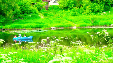 People rowing in a blue boat along summer river Footage