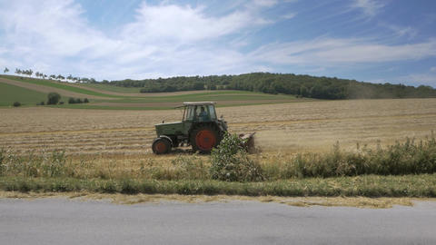 Tractor plowing, gathering wheat field in slow motion Archivo