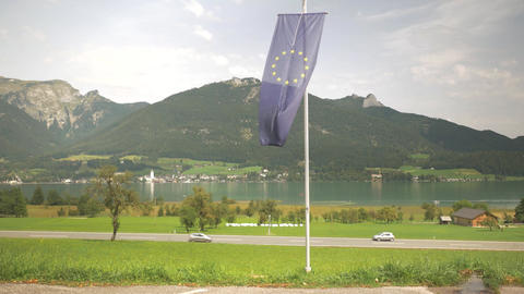 European Union Flag with a highway, lake and mountains view Footage