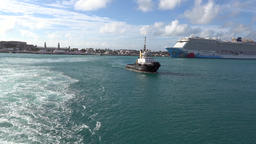 Bermuda Royal Naval Dockyard tail wave with pilot boat and cruise liner Filmmaterial