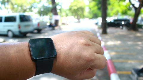 Close up shot hands of man using smart watch in car parking nature public park Footage