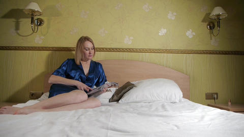 Beautiful blonde girl lying on the bed and reading a magazine Footage