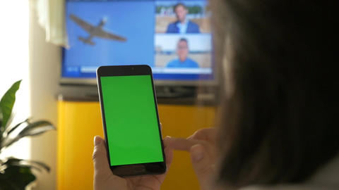 A woman is watching TV, and is holding a smartphone with a green screen. On the Footage