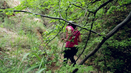 Young girl walking alone on a trail in a deciduous forest. A walk throug the for Footage