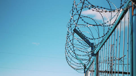 Barbed wire fence against the sky. Prison fencing, cameras, fence of the Footage
