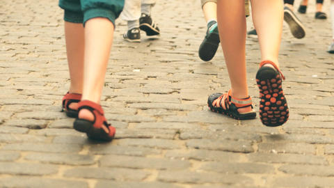 Boys wearing shorts and sandals walk on cobblestone pavement ビデオ