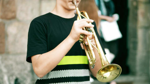 Unidentified boy playing the trumpet on the street Footage