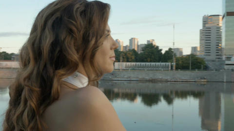 A beautiful girl in white clothes meets the dawn on the city embankment. Early Footage
