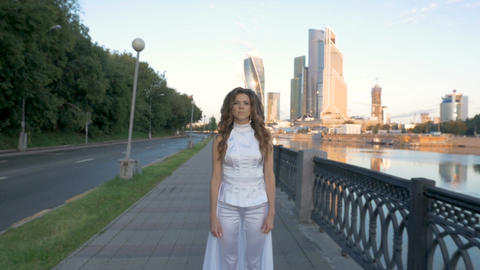 A beautiful girl with long hair in white clothes is walking along the city Footage