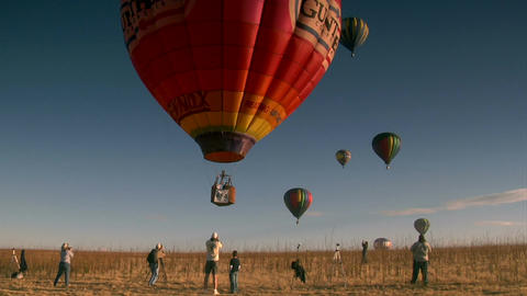 Colorful hot air balloon liftoff with spectators taking photos Footage