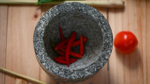 Top view hands of woman putting red hot fresh chilli and garlic in to mortar Footage