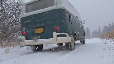 Volkswagen bus driving through countryside in blizzard Footage