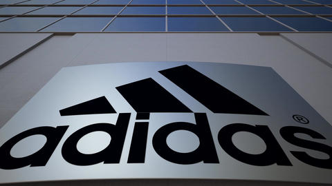 Outdoor signage board with Adidas inscription and logo. Modern office building Footage