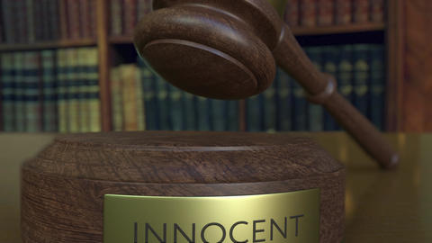 Judge's gavel falling and hitting the block with INNOCENT inscription Footage