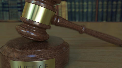 Judge's gavel and block with JUSTICE inscription Footage