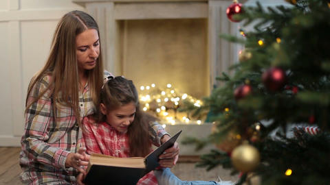 Mother reading book to daughter near xmas tree 画像