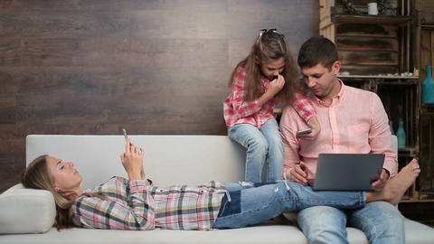 Family busy with electronic devices on sofa Live Action