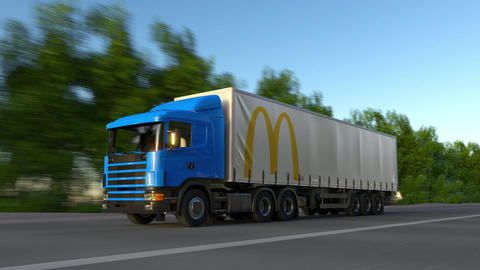 Freight semi truck with McDonald's logo driving along forest road, seamless loop Footage