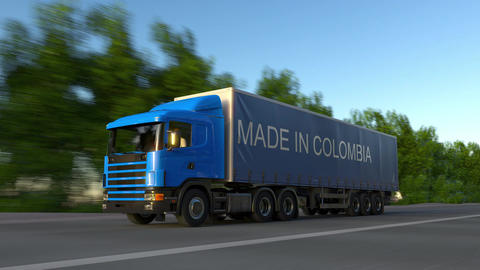 Speeding freight semi truck with MADE IN COLOMBIA caption on the trailer Live Action