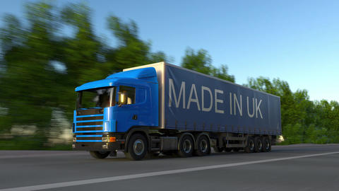 Speeding freight semi truck with MADE IN UK caption on the trailer Live Action