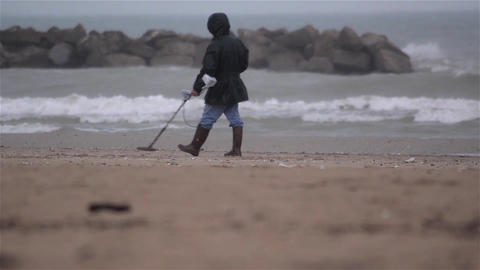 Seeker of precious metals on a deserted beach on the outskirts of town 3 Footage