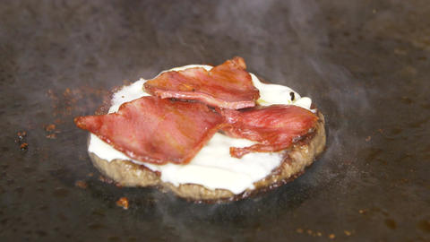 Closeup Cutlet with Cheese and Bacon Fried on Metal Surface Footage