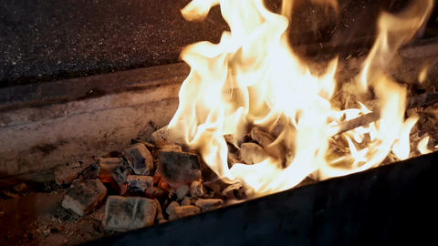 Man mixes the coals in the grill and they burn Footage