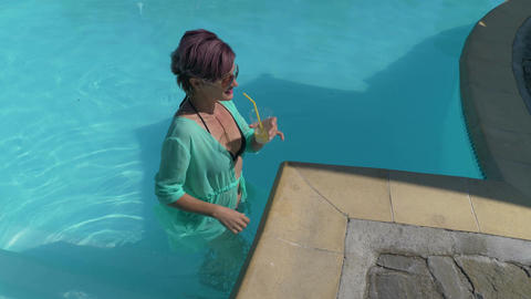 Beautiful attractive mature middle aged lady cools in pool in a summer day Footage