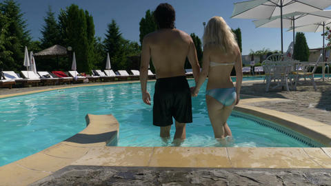 Lovers couple holding hands enter the pool together Footage