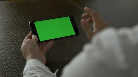 Woman holding a mobile phone with a green screen. For your video content Image