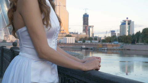 A young woman in a white suit is standing on the city embankment Footage