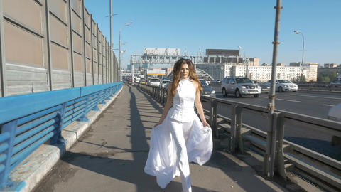 A beautiful woman in a white suit walks along the road. Intensive movement of Footage