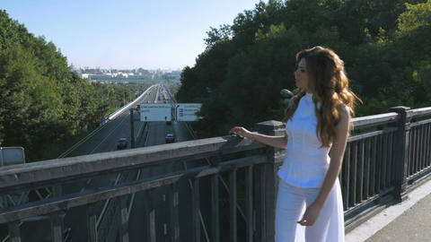 A young woman with long hair walks along the pedestrian bridge. She looks at the Image