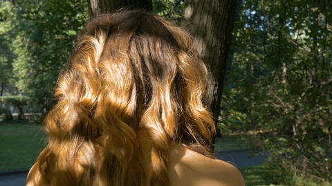Young beautiful woman with red hair is walking in the park Footage