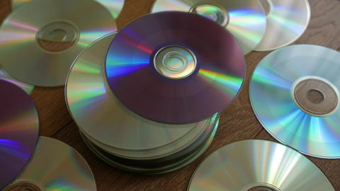 Optical Discs falling onto pile of DVDs or CDs Footage