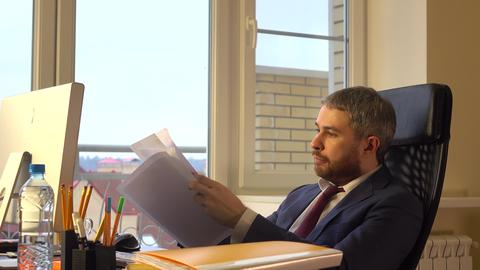 Focused bearded businessman reading business papers Photo