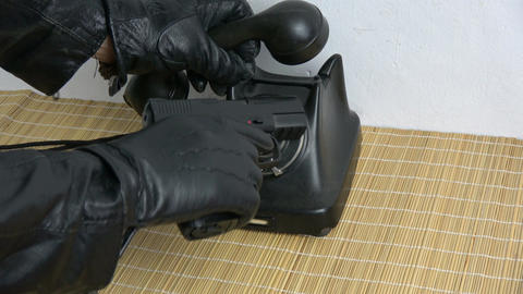 Gangster hand with glove dialing ancient telephone dial with hand gun pistol Footage