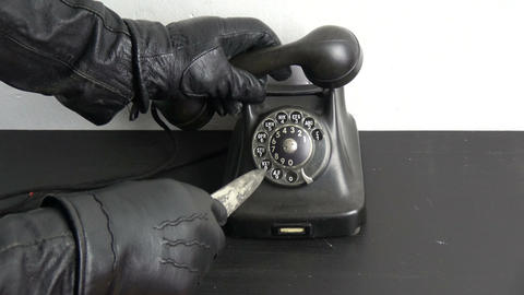 Gangster hand with leather glove dialing ancient telephone dial with vintage Footage