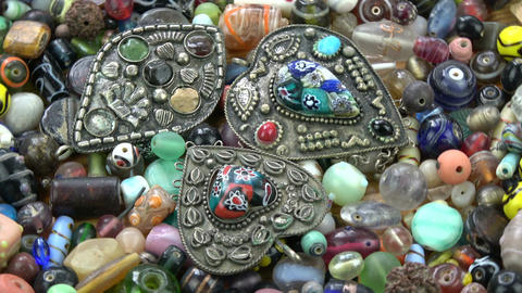 Rotating various indian ancient pendants on old beads background Footage