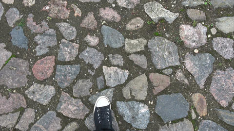 Walking on cobblestone road with plimsols Footage