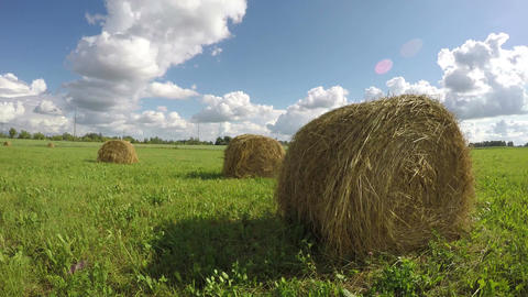 clouded summer sky over country field with haystacks and clouds. Time lapse Footage