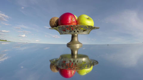 vintage vase with fruits on mirror and clouds motion. Time lapse Archivo