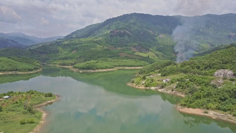 Drone Approaches Green Hills behind Lake with Controlled Fire Footage