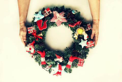 A decorated Christmas wreath in the hands of a woman. Isolated on white Fotografía